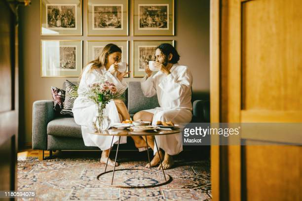 couple in bathrobes drinking coffee while enjoying breakfast at hotel - hotel breakfast stock pictures, royalty-free photos & images
