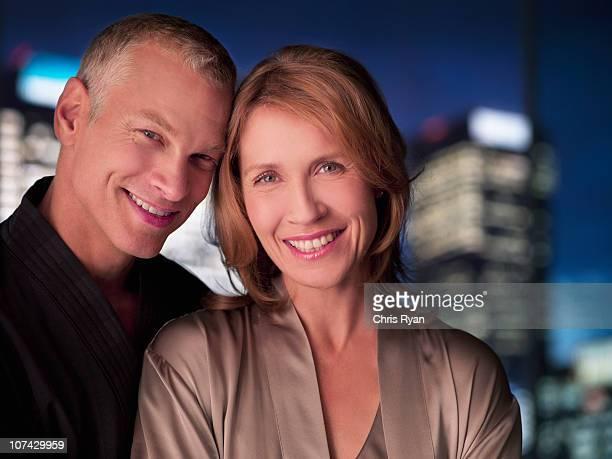 Paar in Bademäntel umarmen mit Lichtern der Stadt im Hintergrund.