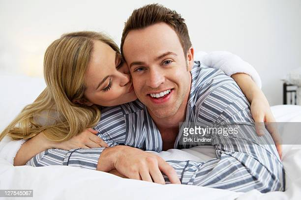Couple in bathrobes kissing on bed