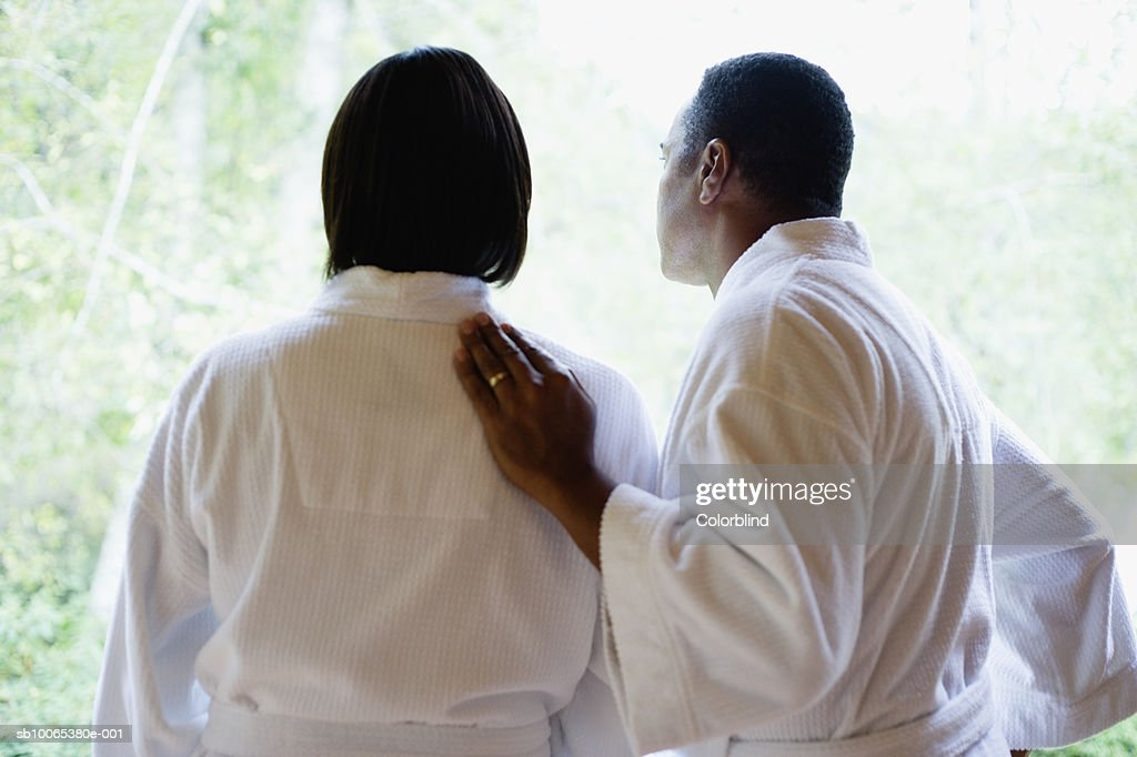 Couple in bathrobes looking through window, rear view : Foto stock