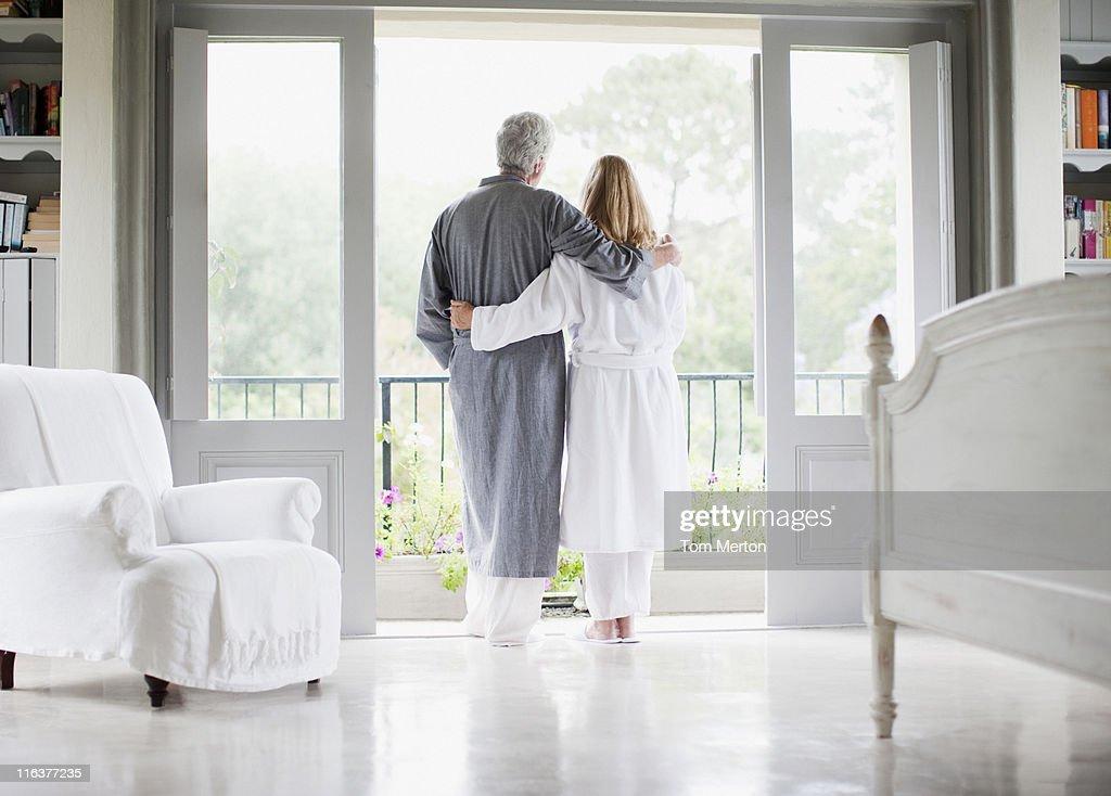 Couple in bathrobes standing in balcony doorway : Stock Photo