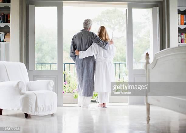 couple in bathrobes standing in balcony doorway - bathrobe stock pictures, royalty-free photos & images