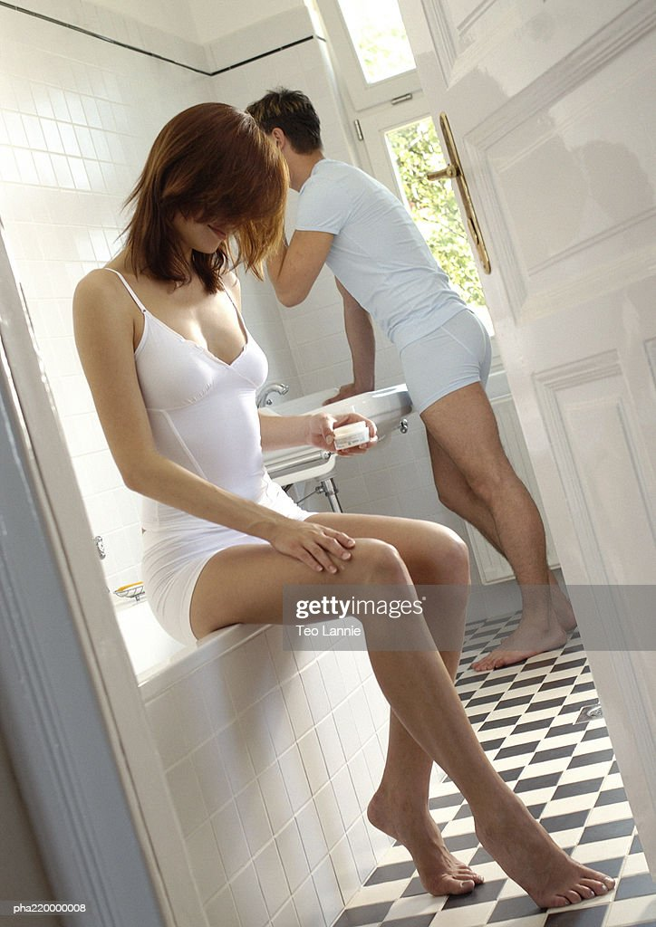 Couple in bathroom, man shaving, woman holding cream. : Stockfoto