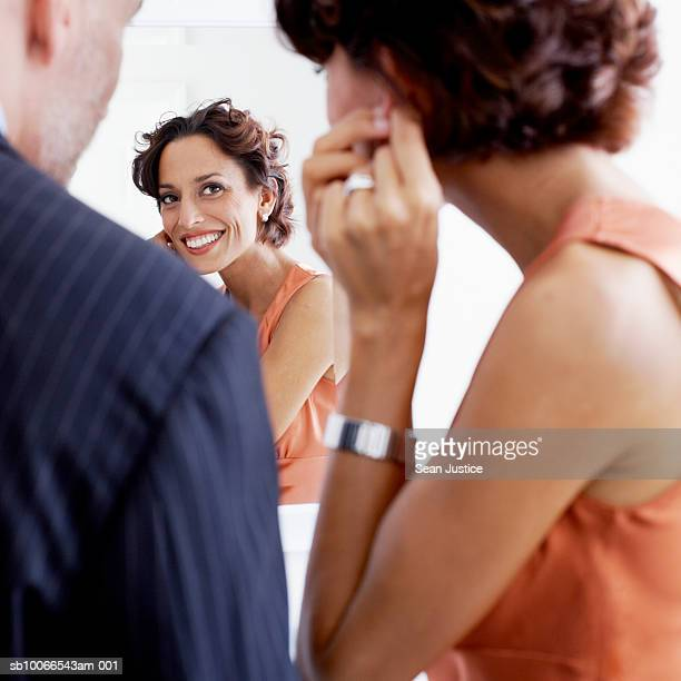 Couple in bathroom, woman looking in mirror and fixing earring