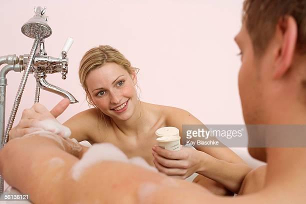 Couple in bathtub, she lathering him