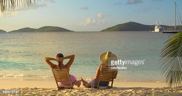 カップルはビーチチェア、足を絡めるながら、サンセット