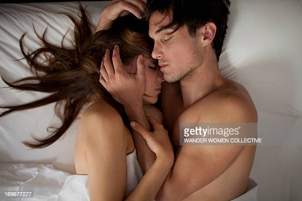 couple in bed cuddling intimately asleep - pareja abrazados cama fotografías e imágenes de stock