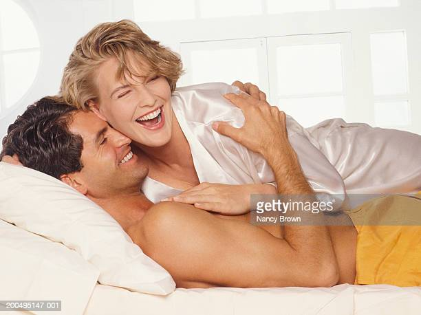 Couple in bed embracing, smiling, close-up
