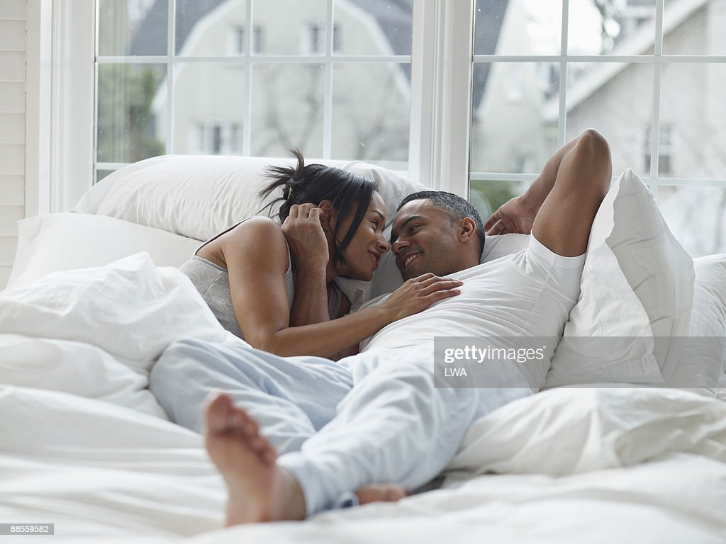 Couple In Bed, Gazing Into Each Other's Eyes : Stock Photo