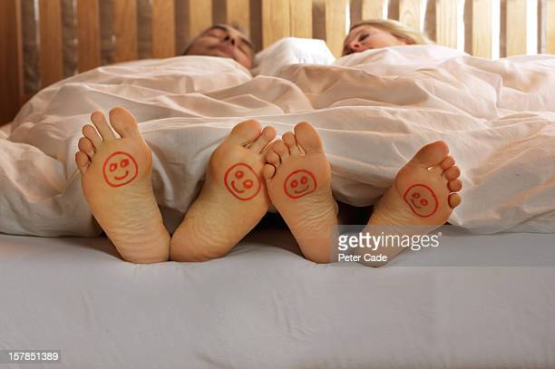 Couple in bed, happy faces drawn on feet