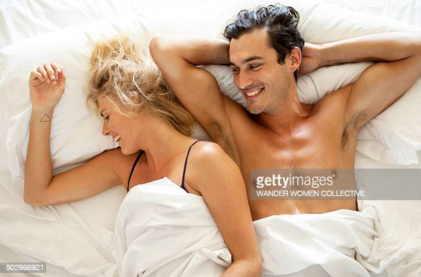 Couple in bed laughing in white sheets