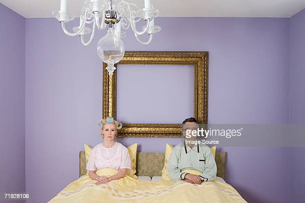 Couple in bed looking miserable