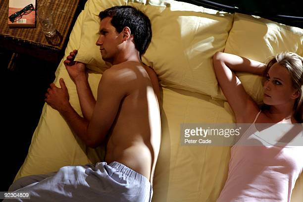 couple in bed, man wit back turned