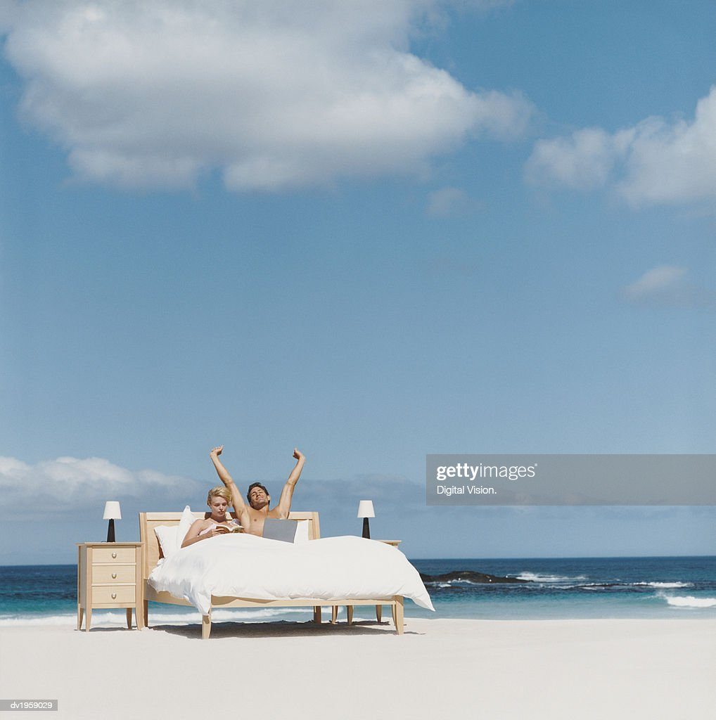 Couple in Bed on a Beach, Man Stretching His Arms : Stock Photo
