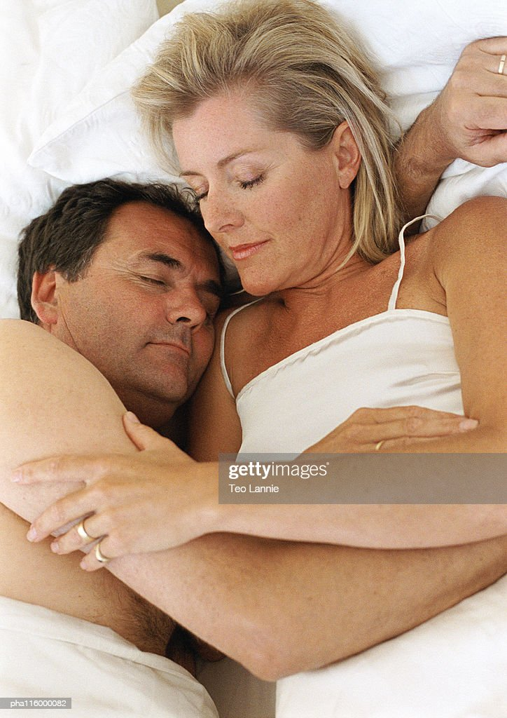 Couple in bed sleeping arm in arm : Stockfoto