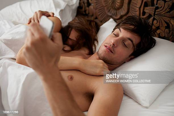 couple in bed texting whilst girlfriend is asleep - verhältnis stock-fotos und bilder