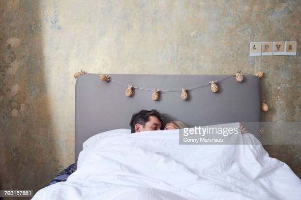 couple in bed, under the covers, kissing - couple lit photos et images de collection