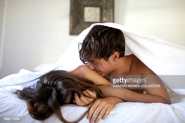 couple in bed under white sheets kissing - couple lit photos et images de collection