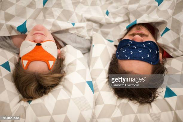 couple in bed wearing eye masks - couple sleeping stock pictures, royalty-free photos & images