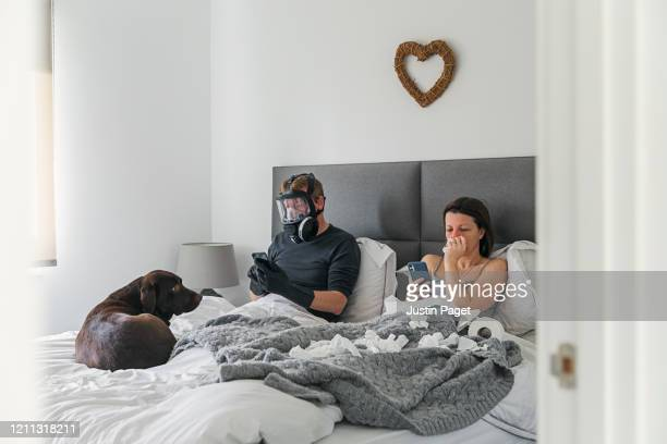 couple in bed. wife has the flu. husband isn't taking any risks..! - casal heterossexual - fotografias e filmes do acervo