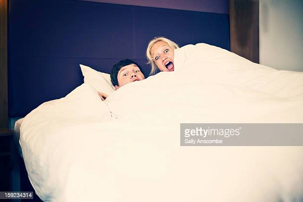 Couple in bed with surprised faces
