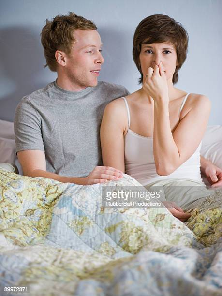 couple in bed with woman holding her nose