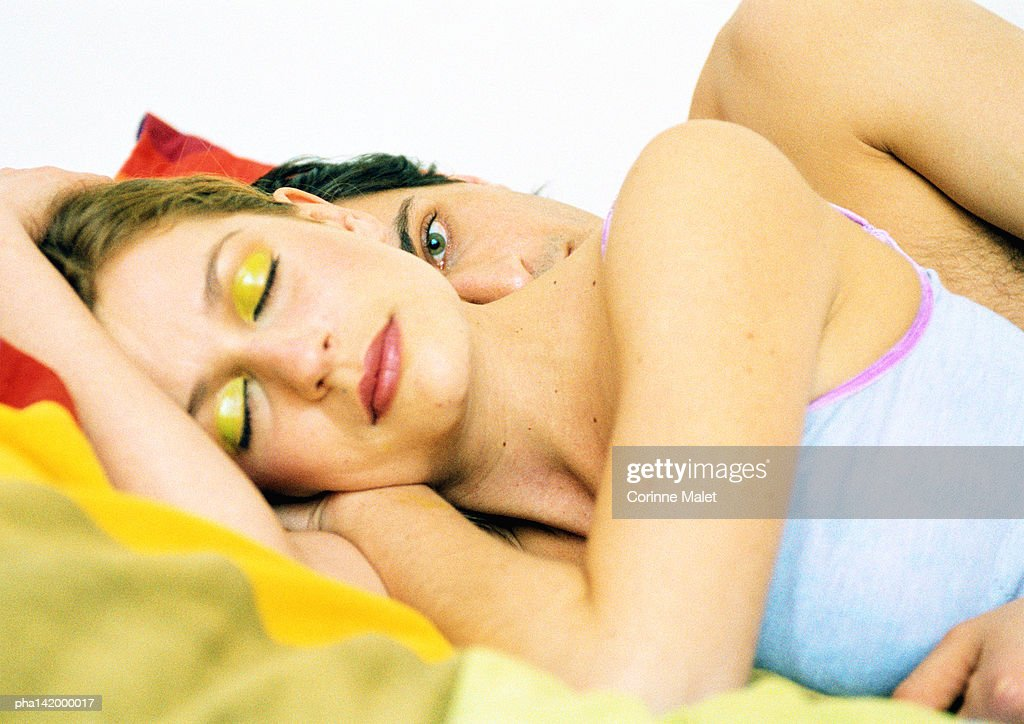 Couple in bed, woman's eyes closed, behind her, man's eyes open, side view. : Stockfoto