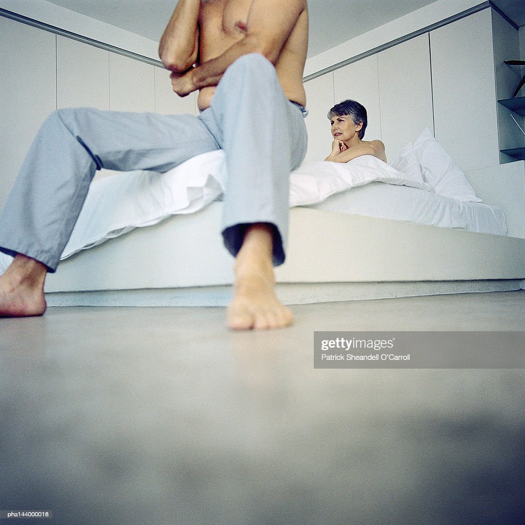 Couple in bedroom, man sitting at end of bed, low angle view : Stockfoto