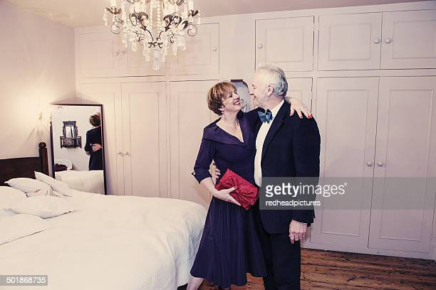 Couple in bedroom, mature woman with arm around senior man