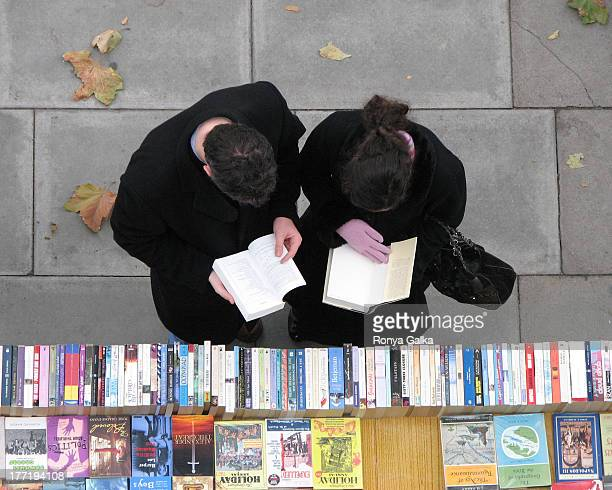 Couple in black winter coats reading books at London's Southbank, Winter 2007