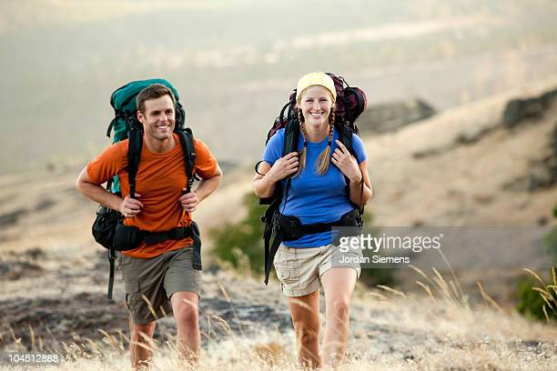 Couple in bright colors hiking a grassy hillside.