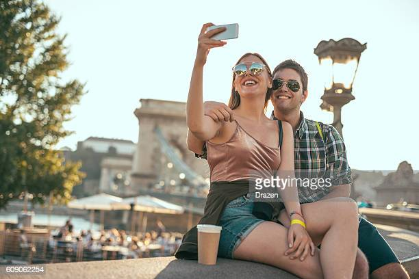 couple in budapest, taking selfie near chain bridge - ponte széchenyi lánchíd - fotografias e filmes do acervo