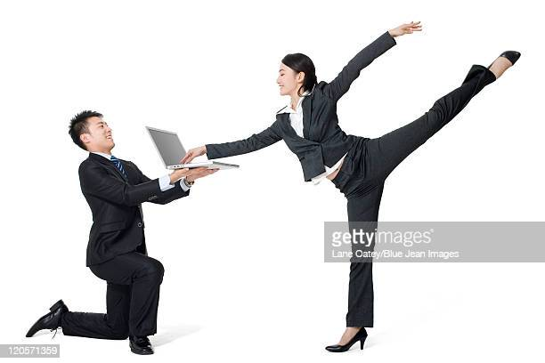 a couple in business-wear dancing with a laptop - 足を開く ストックフォトと画像