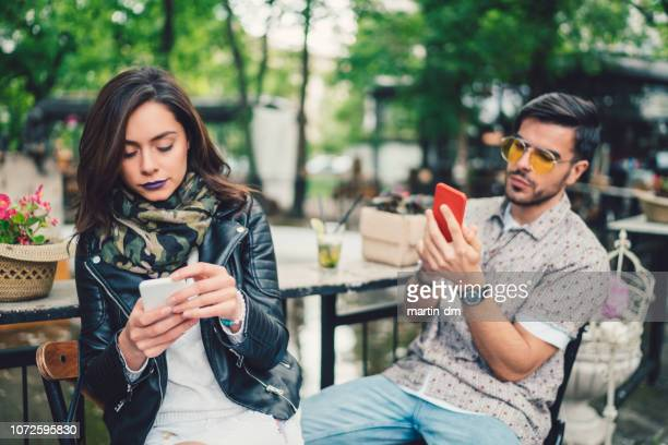 couple in cafe using smartphones and not talking - ignoring stock pictures, royalty-free photos & images