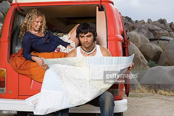 Couple dans un camping-car van lire une carte