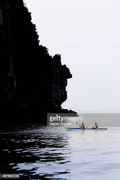 couple in canoe rowing into karst shadows - merten snijders photos et images de collection