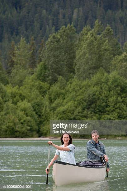 Couple in canoe rowing on river
