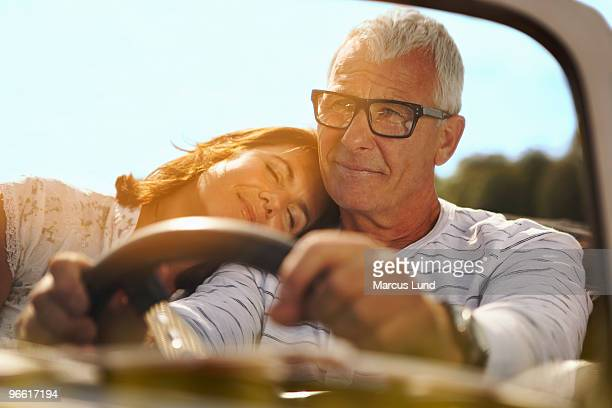 Couple in car, her head on shoulder