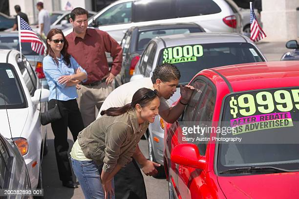 Couple in car lot watching son and daughter (17-19) looking at car