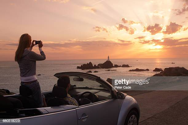 Couple in car taking photo of coastal sunset