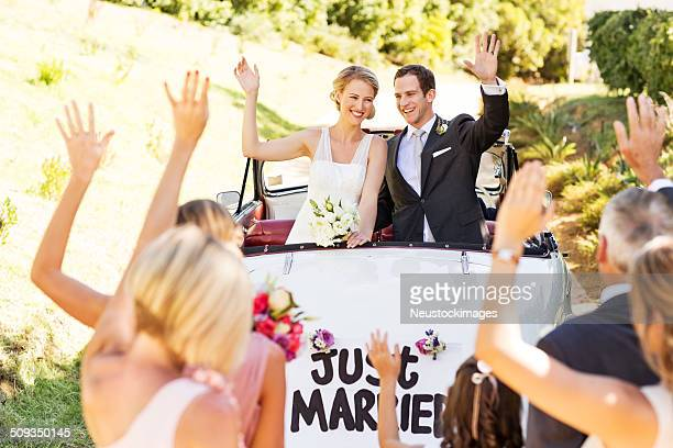 Couple In Car Waving At People