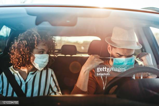 couple in car wearing hygienic mask to prevent the virus - driving mask stock pictures, royalty-free photos & images