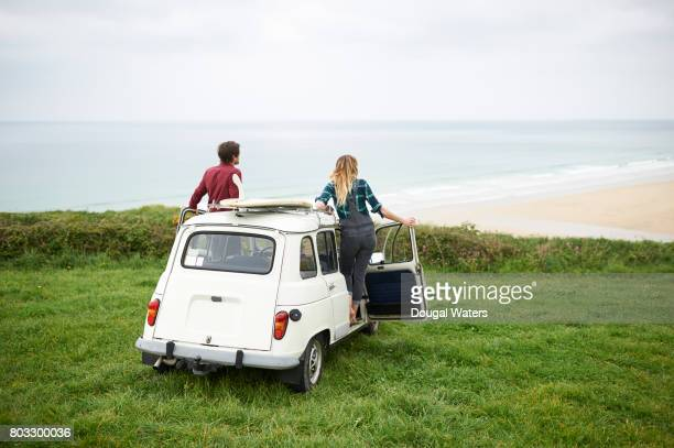 Couple in car with surf board overlooking sea on Atlantic coast.