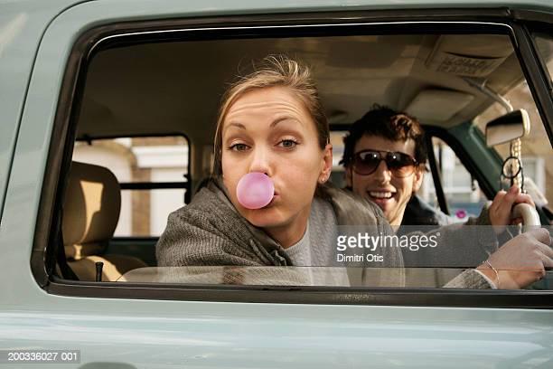 Couple in car, woman blowing bubble, portrait