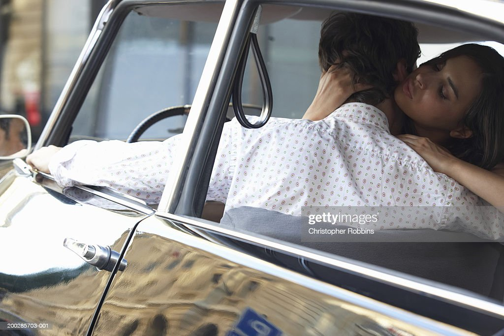 Couple in car, woman embracing man driver's seat, rear view : Stock Photo