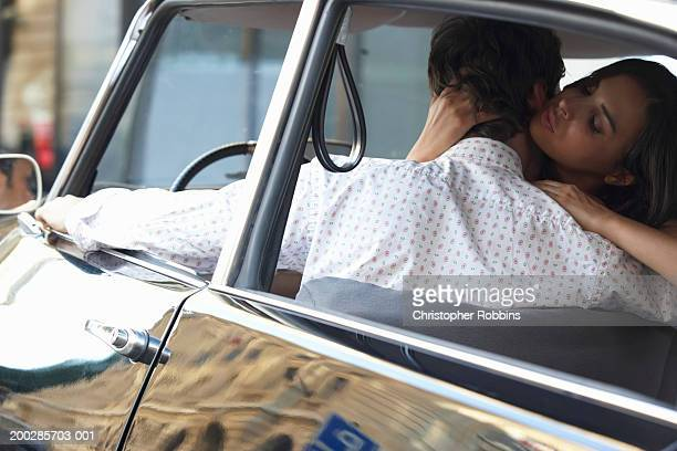 Couple in car, woman embracing man driver's seat, rear view