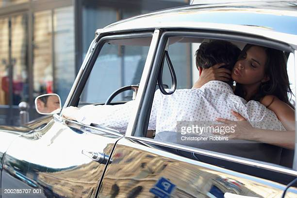 Couple in car, woman embracing man, eyes closed, rear view