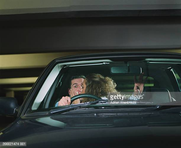 Couple in car, woman leaning over to kiss man, view through windscreen