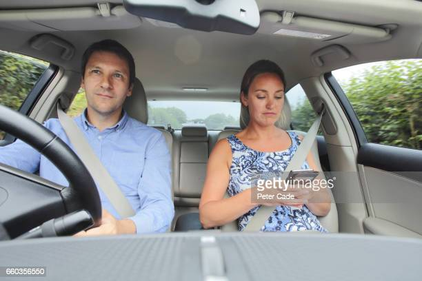 Couple in car, woman looking at phone