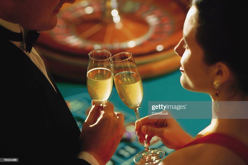 Couple in casino toasting champagne : Stockfoto